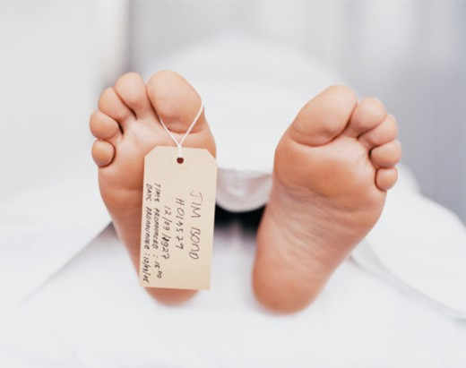 Name Tag Hanging From the Foot of a Dead Body Under a Sheet : Stock Photo