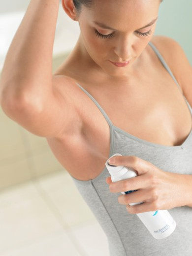 Woman Using a Spray Can Deodorant : Stock Photo