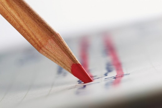 Close Up of a Red Colouring Pencil Crossing Out Handwriting on a Piece of Paper : Stock Photo