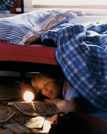 Stock Photo: 1527R-03036 Child Lying on Floor Under Bed Reading by Flashlight