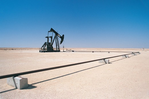 Stock Photo: 1527R-03218 Pipeline Connecting to a Nodding Donkey in the Desert