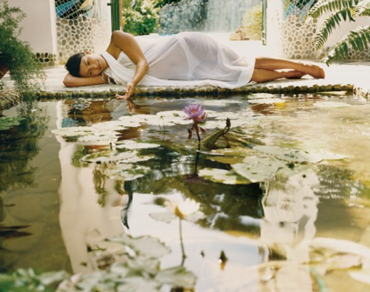 Stock Photo: 1527R-03272 Young Woman Lying in a Courtyard on a Tiled Floor at the Edge of a Pond