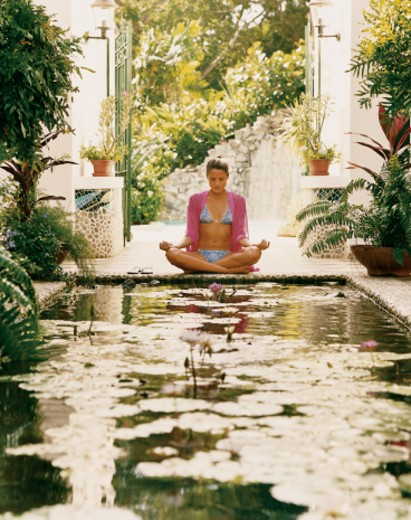 Young Woman Sitting in the Lotus Position at the End of a Pond in a Courtyard : Stock Photo