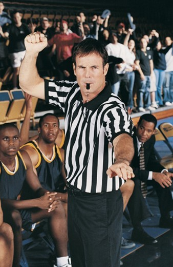 Referee Blowing His Whistle on a Basketball Court in Front of the Stands : Stock Photo