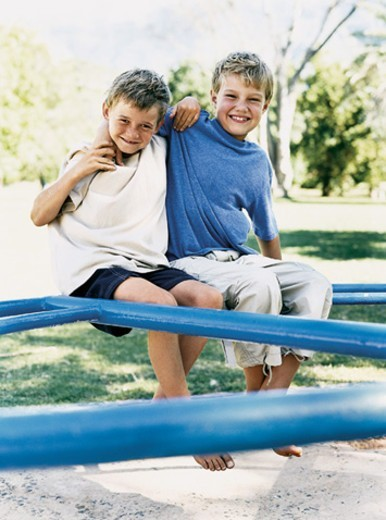 Two Boys Sitting With Their Arms Around Each Other : Stock Photo