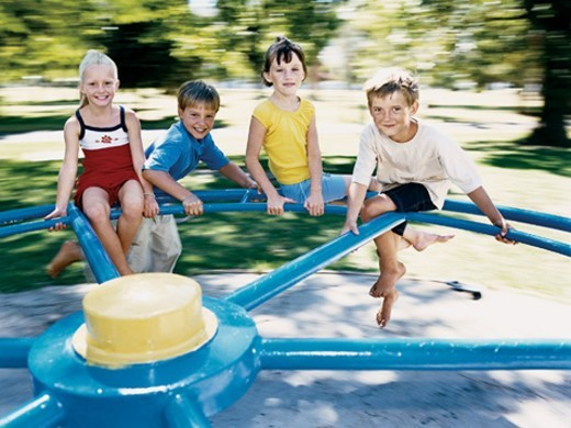 Four Children Playing on a Roundabout : Stock Photo