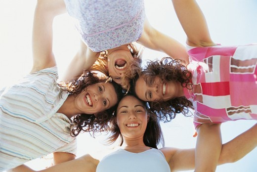Stock Photo: 1527R-0501 Portrait of Four Smiling, Young Women Looking Down With their Arms Around Each Other