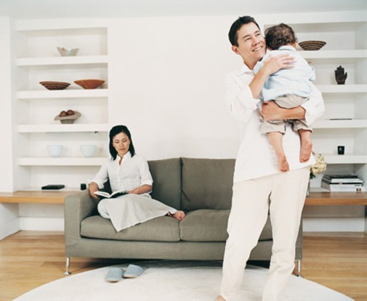 Father Carrying His Young Son in the Living Room in Front of a Woman Sitting on a Sofa Reading a Book : Stock Photo