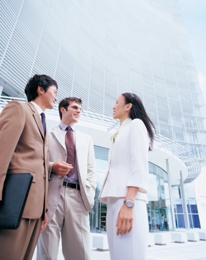 Three Businesspeople Standing Outside an Office Block Talking : Stock Photo
