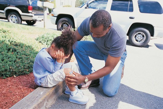 Stock Photo: 1527R-05541 Father Putting a Plaster on his Sons Knee