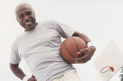 Low Angle View of Elderly Man Standing Holding a Basketball : Stock Photo