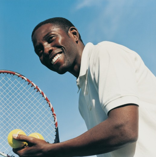 Young Man Playing Tennis Holding a Racket and Tennis Balls : Stock Photo
