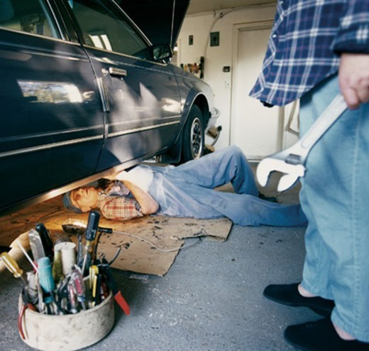 Elderly Man Lying Under a Car, Person Standing Holding a Spanner : Stock Photo