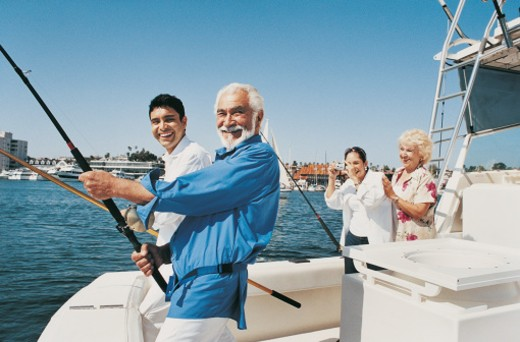 Two Men Holding Fishing Rods at the Stern of a Motorboat as a Woman Photographs Them : Stock Photo