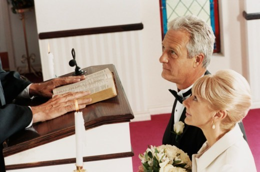 Senior Bride and Groom Standing in Church by a Priest at a Wedding Ceremony : Stock Photo