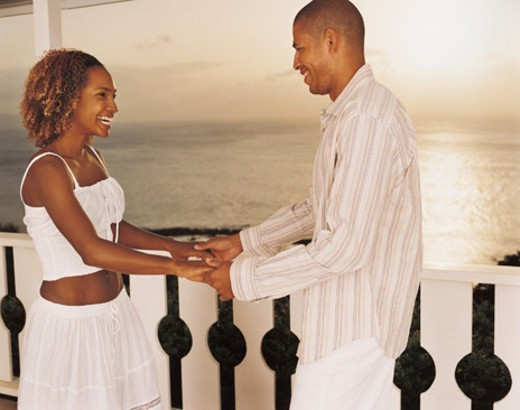 Man and Woman Dancing on a Balcony Holding Hands : Stock Photo