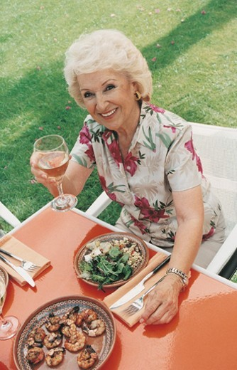 Stock Photo: 1527R-06546 Elevated View of a Senior Woman Having Lunch on Her Lawn