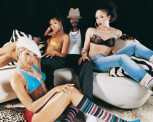 Stock Photo: 1527R-06635 Four Young, Glamourous Adults Around a Sofa