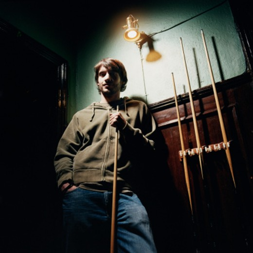Young Man Standing in a Pub and Holding a Cue : Stock Photo