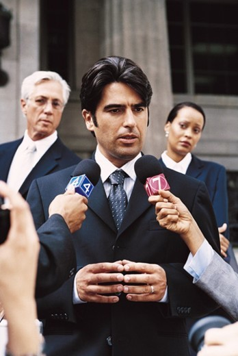 Stock Photo: 1527R-0667 Man in a Suit Being Interview by TV Reporters