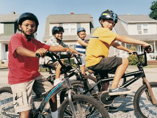 Stock Photo: 1527R-0697 Portrait of Four Children on Mountain Bikes Wearing Cycling Helmets on a Suburban Road
