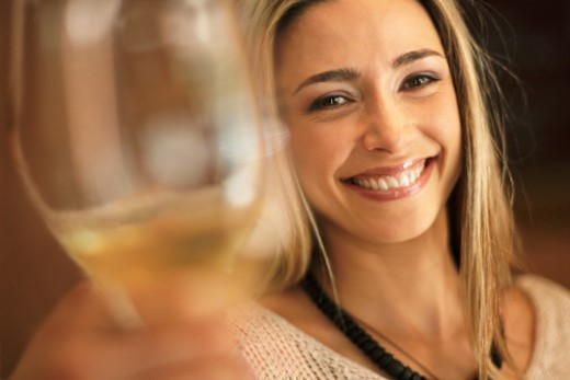 Blonde Woman With Long Hair Raising Her Glass in Differential Focus : Stock Photo