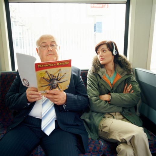 Young Woman Sits With her Arms Crossed Staring at an Overweight Businessman Sitting Next to Her Who is Reading a Magazine : Stock Photo