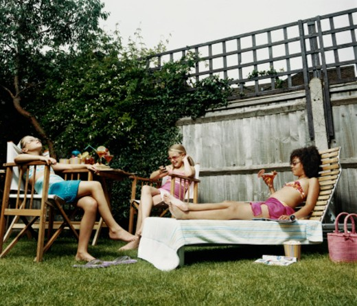 Stock Photo: 1527R-07472 Three Teenage Girls Sit and Relax in Garden