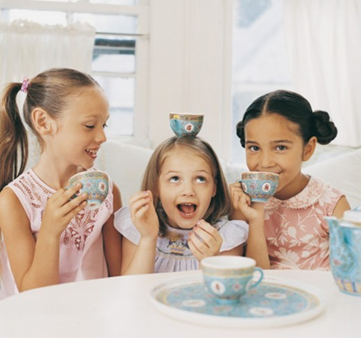 Stock Photo: 1527R-07497 Three Girls Sitting Side by Side Having a Tea Party And Making Fun