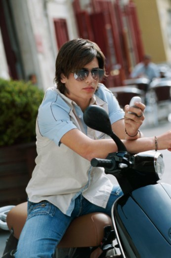 Stock Photo: 1527R-07879 Teenager Sitting on a Stationary Moped Holding a Mobile Phone