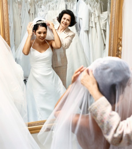 Stock Photo: 1527R-08075 Senior Woman Helping Her Daughter Try on a Wedding Dress in Front of a Mirror in a Bridal Shop