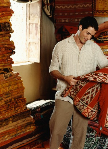 Stock Photo: 1527R-08083 Man Examining Rugs in a Shop in Morocco