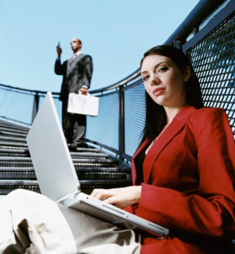 Low Angle View of a Businesswoman Sitting on Steps Using Her Laptop Computer and Businessman Standing in the Background : Stock Photo
