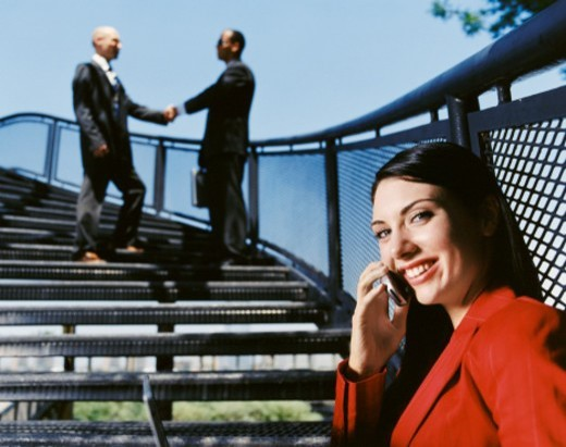 Stock Photo: 1527R-08204 Businesswoman Sits on Steps Talking on Her Mobile Phone and Businessmen in the Background Shake Hands