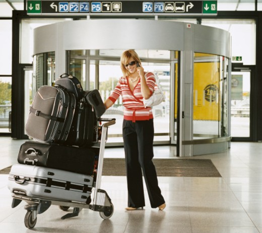 Stock Photo: 1527R-08382 Woman at an Aiport Pushing a Baggage Trolley and Using a Mobile Phone