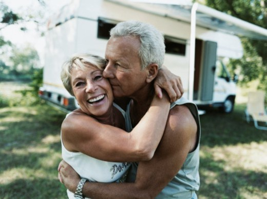 Stock Photo: 1527R-08403 Couple Embrace With A Motor Home In The Background