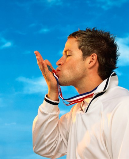 Profile Portrait of an Athlete Kissing His Gold Medal : Stock Photo