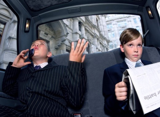 Two Boys Dressed as Businessmen in the back of a Taxi, one Reading a Newspaper the Other Gesturing Angrily and Using a Mobile Phone : Stock Photo