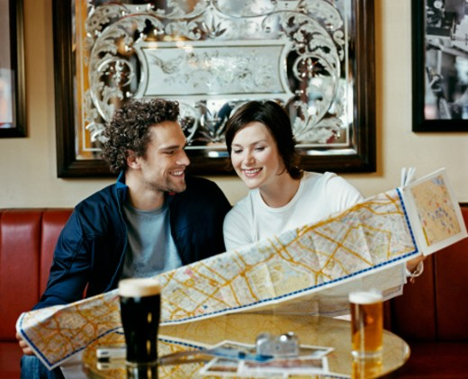 Stock Photo: 1527R-08740 Couple in a Pub Holding a Map