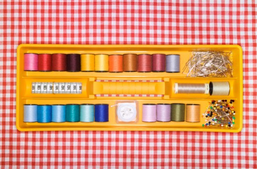 Stock Photo: 1527R-08866 Sewing Box Filled with Reels of Thread, on a Checked tablecloth