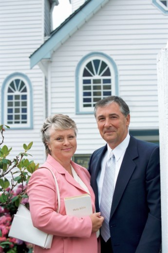 Couple Standing Side By Side Outside of a Church, with the Woman Holding a Bible : Stock Photo