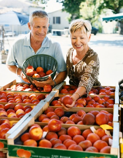 Stock Photo: 1527R-08904 Mature Couple Buy Nectarines at an Outdoor Market in Provence