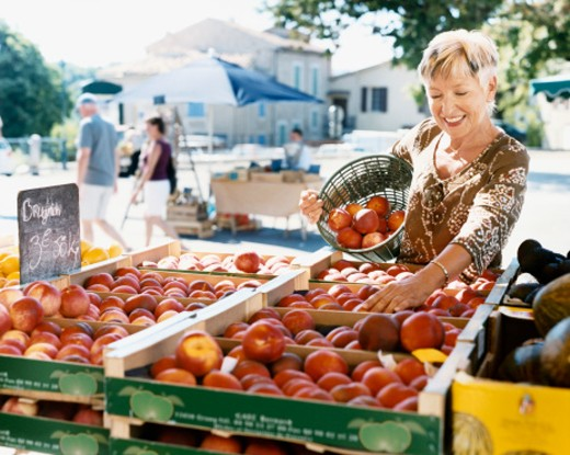 Mature Woman Picks Nectarines at an Outdoor Market in Provence : Stock Photo
