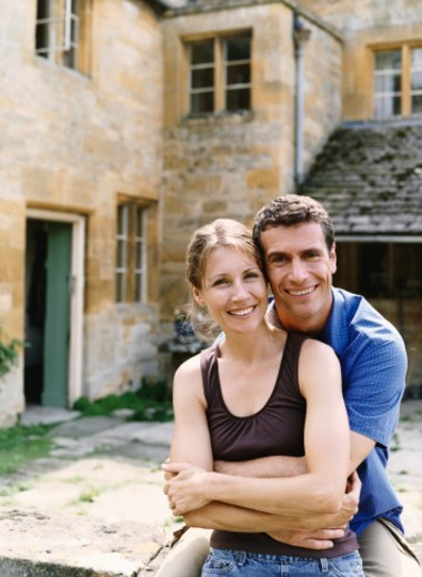 Couple Sitting on a Wall in Front of a House : Stock Photo