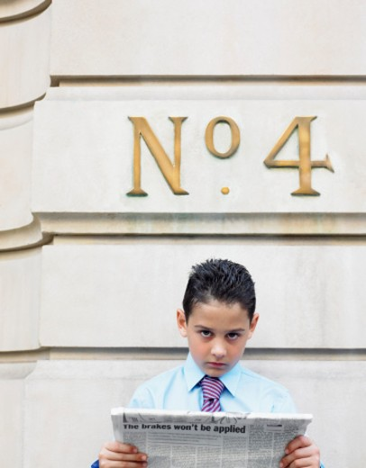 Serious Young Boy Dressed as a Businessman Holding a Newspaper Below a Street Number Sign : Stock Photo