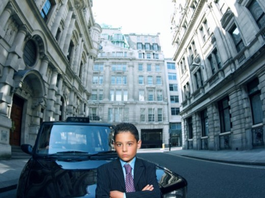 Stock Photo: 1527R-09322 Boy Dressed as a Businessman Standing in a Road with a Taxi Behind him