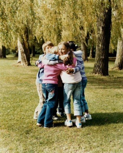 Stock Photo: 1527R-09446 Five Children Standing Outdoors in a Park Huddled Together
