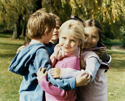 Stock Photo: 1527R-09447 Five Children Standing Outdoors in a Park Huddled Together