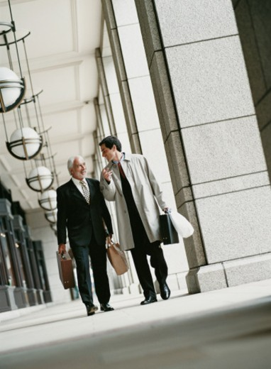 Stock Photo: 1527R-09986 Two Businessmen Walking Side by Side and Talking