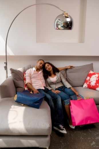 Young couple leaning against each other on sofa in shop, eyes closed : Stock Photo